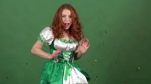Young woman celebrating saint patrick's day on green wall wearing traditional dress dancing among falling confetti