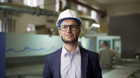 Portrait young male manager of furniture factory in suit and helmet, monitoring process of work