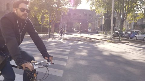 Young hipster man riding bike in Rome city centre with historic ruins and cars wearing sunglasses on sunny day slow motion camera car steadycam