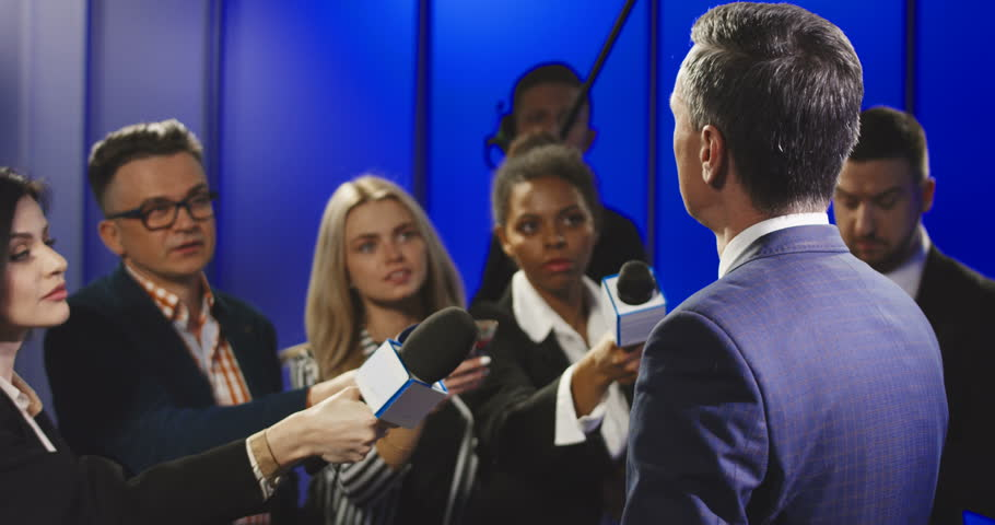 Big group of multiracial journalists with microphones and other technological equipment having interview with middle-aged politician in underlit studio. | Shutterstock HD Video #1007749945