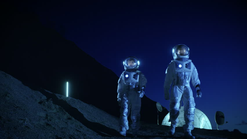 Two Astronauts in Space Suits Exploring Newly Discovered Planet. In the Background Space Base. Futuristic Concept on Space Colonization. Shot on RED EPIC-W 8K Helium Cinema Camera.