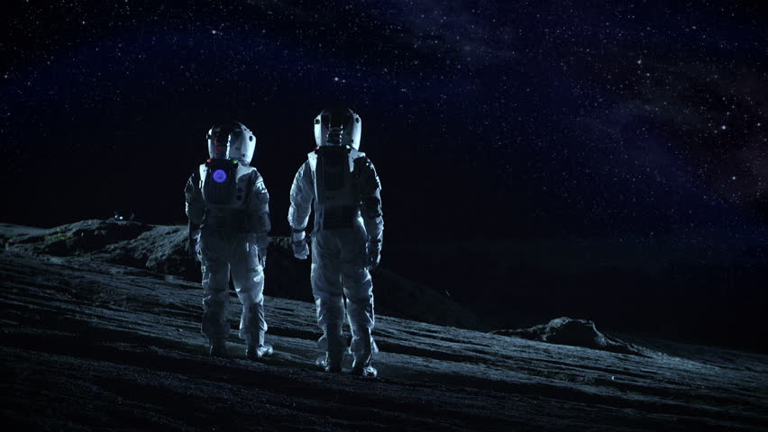 Two Astronauts in Space Suits Stand on the Alien Planets Looking at the Stars and Galaxies. Space Travel and Extraterrestrial Colonization Concept. Shot on RED EPIC-W 8K Helium Cinema Camera.