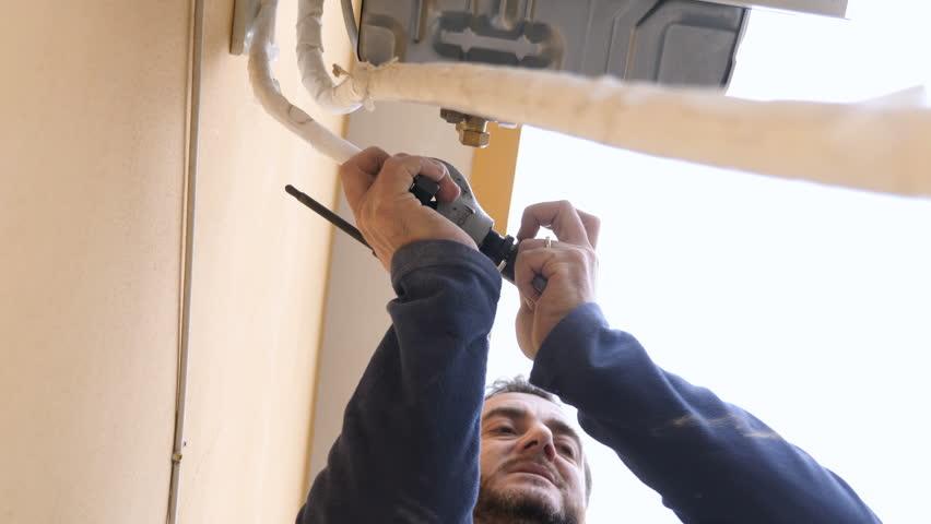 expert technician repairs the air conditioner