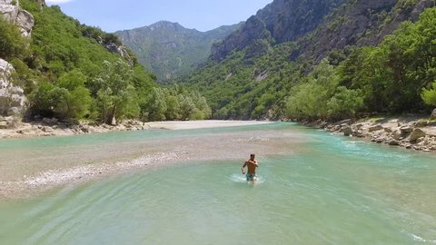 France, Provence, lake Cross, strong young man have a fun in the gorge Verdon, shoot video by means of drone, azure water of the river, the rocky coast with trees