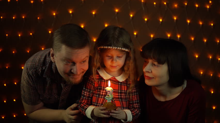 A little girl blows out a candle on a festive cake with her mom and dad, against a background of yellow electric bulbs. | Shutterstock HD Video #1007764645
