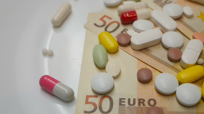close up, colored pills rotating on 50s euro banknotes from the right side #1007781745