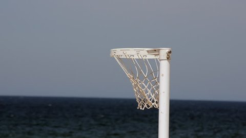 A Close Up shot of a Netball Hoop during the Australian Netfest Competition with the Net blowing in the breeze, set on a beach with the ocean meeting the skyline horizon positioned at lower 1/3rd.