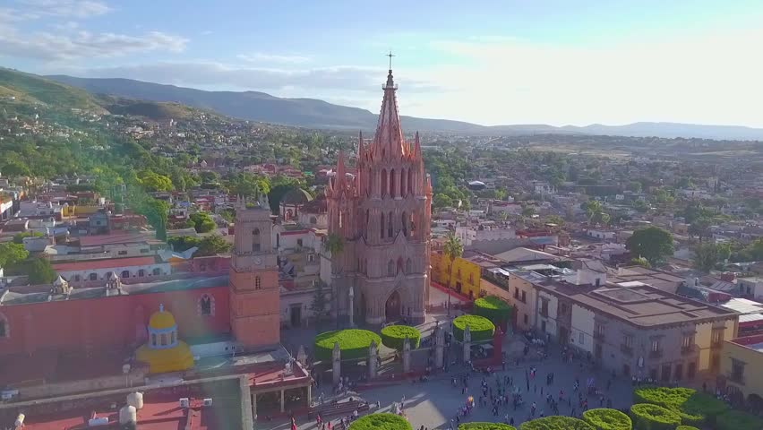 Fly over the magical town of San Miguel de Allende on a clear day with the Parroquia de San Miguel Arcángel in the foreground | Shutterstock HD Video #1007811655