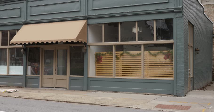 A daytime exterior establishing shot of a typical corner business, bar, cafe, restaurant or souvenir shop in the downtown district of a small city or town. Logos and names removed for general stock us