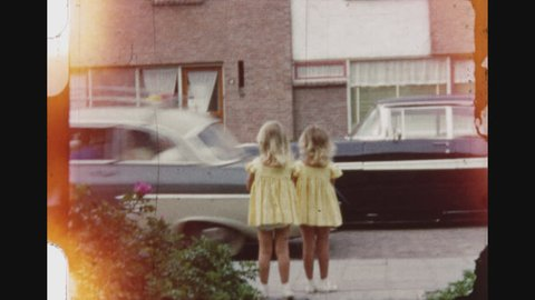 NOORDWIJK, NETHERLANDS, SUMMER 1956. Six Shot Sequence Of Little Blond Twin Girls Dressed In Yellow Joking With The Camera And Running On The Sidewalk.