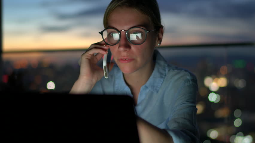 Close up view of businesswoman carefully checks information on laptop computer while talking on mobile phone. Female freelancer busy working at home receiving call and email on netbook | Shutterstock HD Video #1007840545