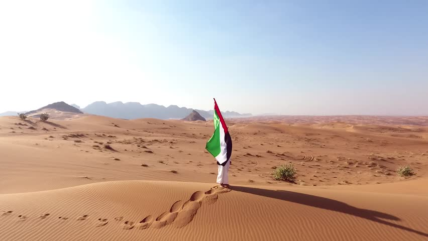 Arab emirati man holding UAE flag and walk in the Dubai Desert | Shutterstock HD Video #1007848525