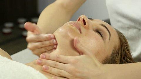 Beautiful woman getting facial massage in spa. facial skin care in beauty saloon. 4K