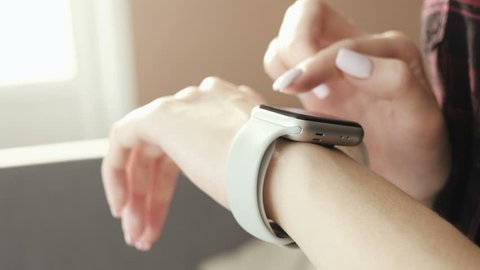 Woman using smartwatch touchscreen wearable technology device. Closeup. Smart watch on female wrist. Pretty girl making gestures on a smartwatch computer device
