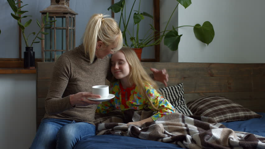 Attenitive mother giving her ill cute daughter a cup of hot tea. Sick little girl in pajamas with high fever lying in bed, coughing and drinking hot tea. Lovely ill child taking a medicine in the bed.