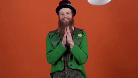 Young man leprechaun celebrating saint patrick's day isolated on orange wall jumping up