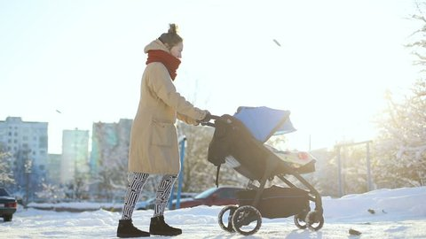 Side view of young mother pushing a baby carriage on the winter snowy street and sunshine on the background. mqternity walk stroll cat pet outside sunny happy parenting child infant boy blue pram