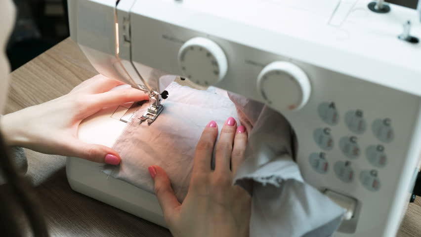 Woman sewing light fabric on a sewing machine close-up. Side view. Top view. | Shutterstock HD Video #1007927785