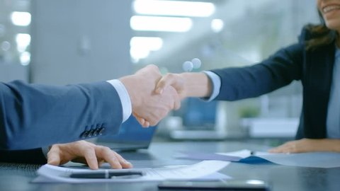In the Office Close-up on Hands of Businesswoman and Businessman while Signing Contracts and Shaking Hands for Finishing Transaction. Stylish People in Modern Conference Room. Shot on RED EPIC-W 8K.