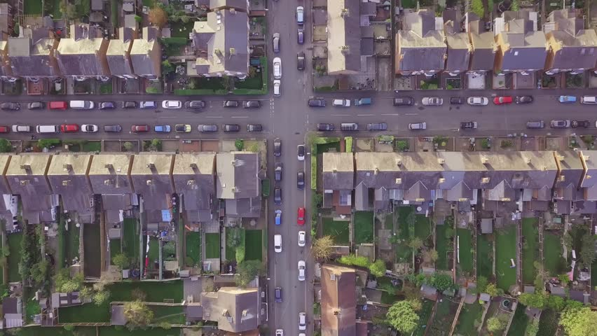 Aerial drone lifestyle concept flying over a street lined with British terraced houses during the golden hour as the sun is setting. Cross roads, a church and people walking and playing feature.