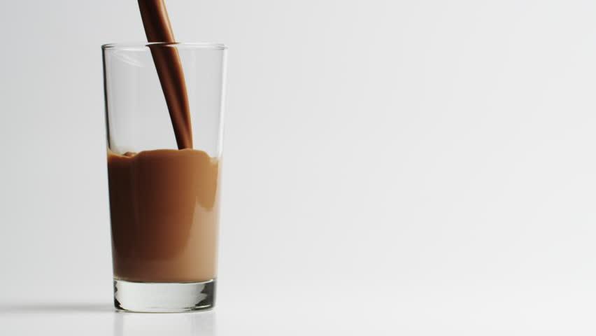 Chocolate milk filling drinking glass, studio