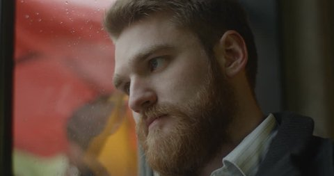 Portrait of the handsome depressed ginger head man with beard sadly looking away and leaning on the window of bus. 4k.