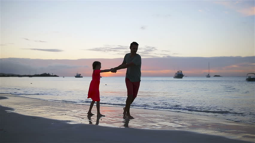 Family fun on white sand. Smiling father and child playing at sandy beach on a sunny day