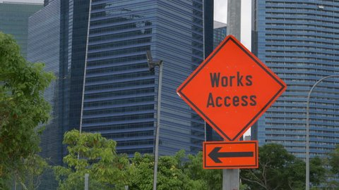 CLOSE UP Works access sign in front of tall glassy skyscrapers in metropolis city. Bright orange traffic sign instructing traffic to turn left and away from construction site next to office buildings.