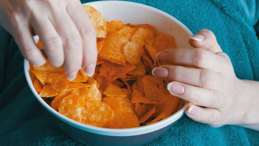 A large plate with potato chips. The woman lies on the couch and eating potato chips, close up view