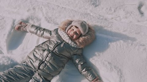 A little girl makes snow angels in snow. Top view.