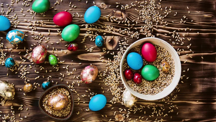 Many Easter beautiful colorful eggs, large and small, lie in wooden plates and on a wooden table. Colorful pastel easter eggs on wooden board background with space vintage toned.