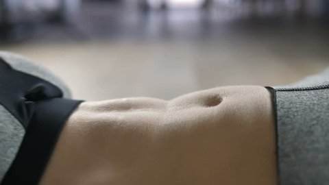 Extreme close-up of woman doing abdominal exercise indoors. Sporty female in sportswear top doing crunches at home on the floor. Sit ups as best exercise for abs.