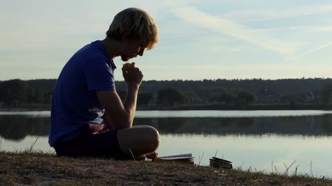 Young student reads a book on a lake bank at sunset in slo-mo