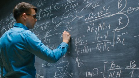 Brilliant Young Mathematician Approaches Big Blackboard and Finishes writing Sophisticated Mathematical Formula/ Equation. Shot on RED EPIC-W 8K Helium Cinema Camera.