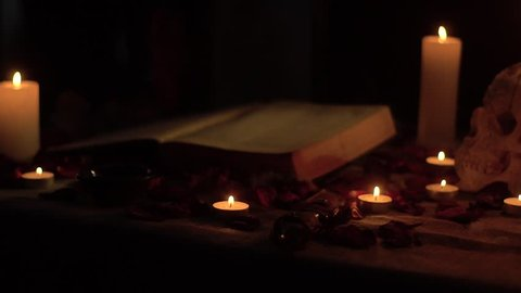 The witch cuts his hand with a ritual knife against the backdrop of a book and a skull by candlelight