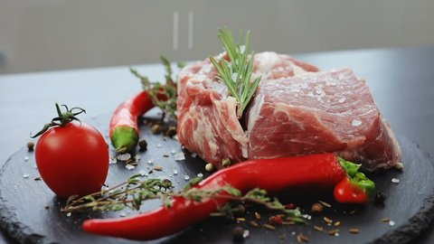 close up side view of raw slices of fresh meat falling salt. salting up spice red hot chilli pepper mexico food herb steak tomato vegetables eco bio product delicious dish cooking tasty meal beef