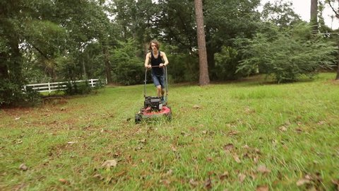 Teenager mowing the lawn for a summer job.