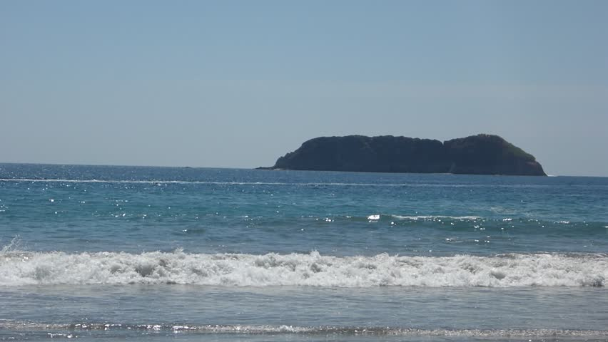 Looking Out Into The Ocean At Playa Espadilla In Costa Rica With Island Rock Outcroppings