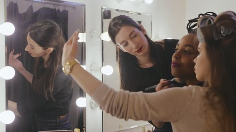 Two woman friends making selfie photo front mirror in dressing room. Professional stylist and man hairdresser making fashion look in beauty saloon