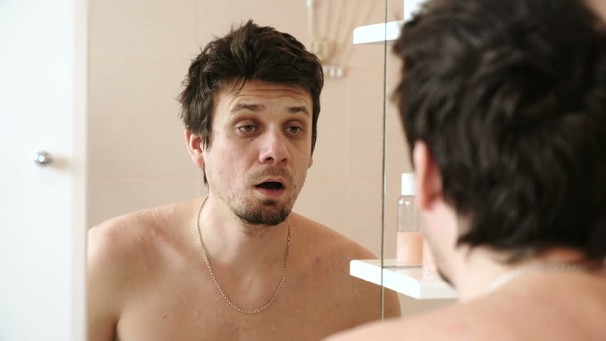Tired man who has just woken looks at its reflection in the mirror, yawns and hits themselves on cheeks, to wake up.
