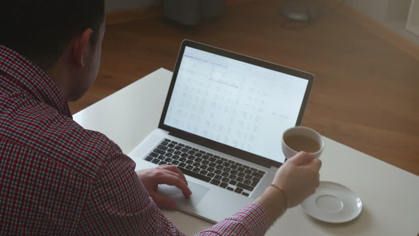 Man in works from home using the top and trackpad. Young business man sitting at table drinking coffee, doing work on computer. 4K | Shutterstock HD Video #1008139195