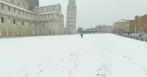PISA, ITALY - MARCH, 1 2018: Extraordinary snowfall in Pisa, Piazza dei Miracoli near the leaning tower. Particular of the Cathedral, the tourists while taking picture and the snow.