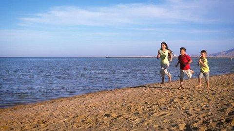 Three kids running at the beach of Red sea, Egypt resort, Sharm el Sheikh, slow motion 250 fps