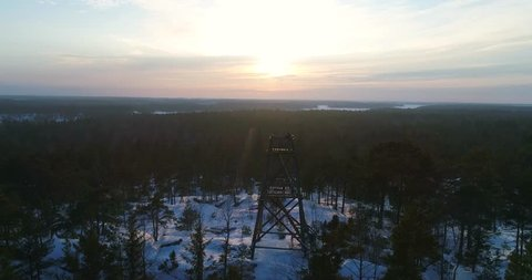 Observation tower, Cinema 4k sideway of a man on a watchtower, with a view of a snowy archipelago landscape, on a cold winter evening dusk, in Uusimaa, Finland