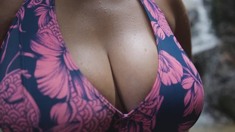 Close up of a young wet sexy woman in bikini shaking boobs with droplets in slow motion. 180fps. 1920x1080