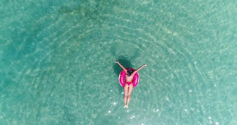 AERIAL. Top view of young pretty sexy girl swimming with pink swimming mattress at the ocean, wearing bikini and sunglasses, view on ocean, relax and having fun on vacation.
