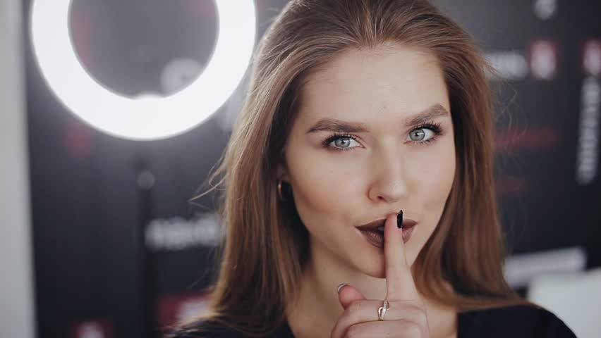 Beauty portrait of sexy young woman with finger on her lips showing hush. Sign of silence