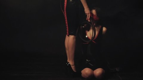 Young submissive woman in latex/ BDSM theme