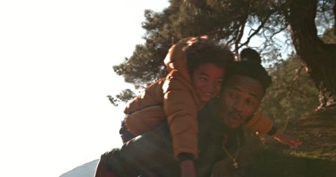 Hipster father and son having fun with piggyback ride and running together in mountain forest
