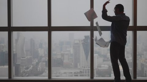 Angry boss on phone throwing contract documents in office